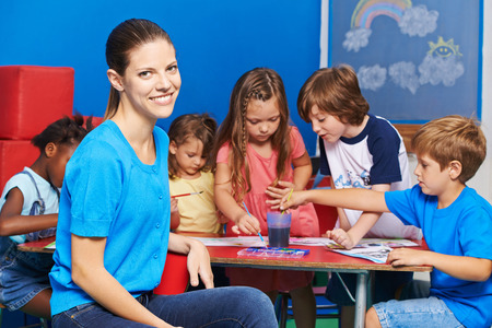 children painting: Woman as nursery teacher in kindergarten with group of children painting at table