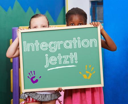 migrant: Two children demanding on chalkboard in German Integration jetzt! (Integration now!)