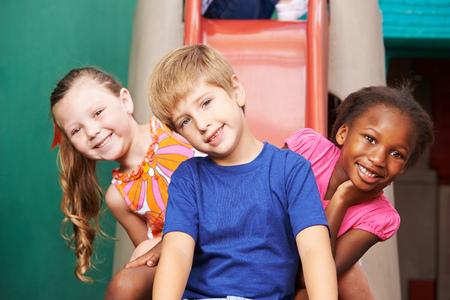 small group: Three happy kids sitting on a slide in kindergarten