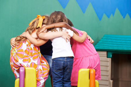 huddle: Children in kindergarten going into huddle to hold a council of war