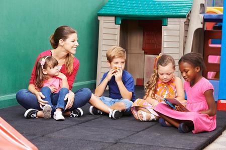 maestra preescolar: Grupo de niños con el maestro de guardería de leer un libro en el preescolar Foto de archivo