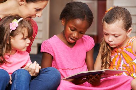 educators: Los niños que están aprendiendo a leer con el maestro cuarto de niños en edad preescolar Foto de archivo