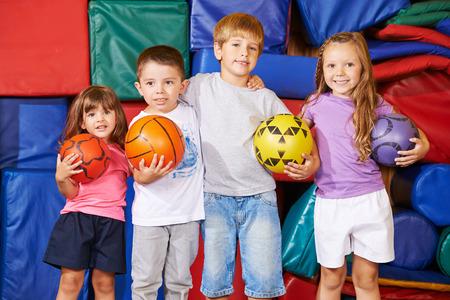 Gelukkige groep kinderen met verschillende ballen in de gymzaal van de kleuterschool
