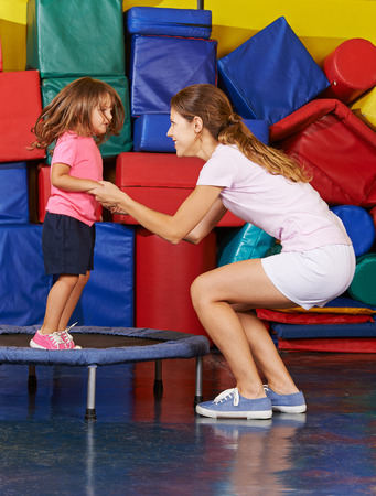 gymnastics: Girl jumping on trampoline with nursery teacher during children sports Stock Photo