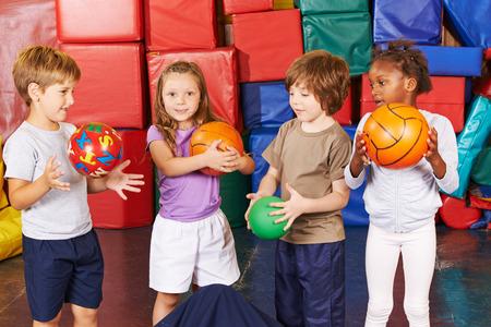 gimnasia: Ni�os que juegan con diferentes bolas en el gimnasio de la educaci�n preescolar