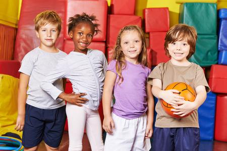 jovenes estudiantes: Los ni�os forman equipo para el juego de pelota en el gimnasio de un jard�n de infantes Foto de archivo