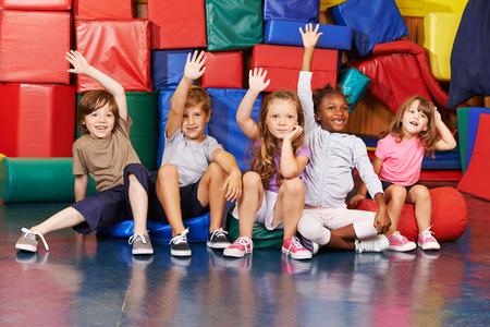 kinder: Ni�os felices que levantan sus manos en el gimnasio de una escuela primaria