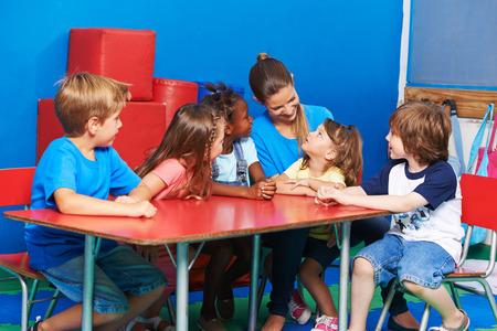 Children in circletime listining to girl talking in kindergarten
