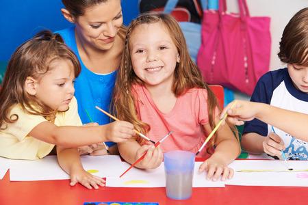 maestra preescolar: Profesor de Arte y niños que pintan imágenes juntas en la escuela primaria
