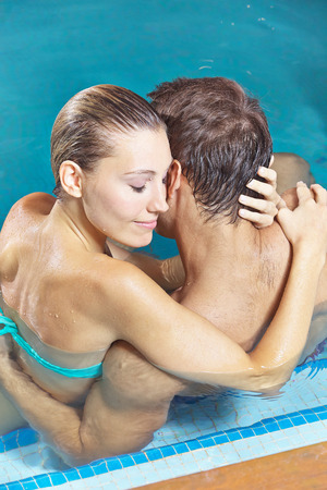 man behind: Happy couple embracing in hotel swimming pool in summer