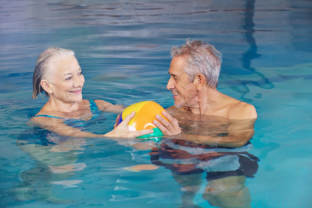 pool game: Happy senior couple playing water ball with beach ball in swimming pool
