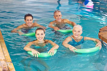 swim: Grupo de gente feliz con fideos de natación haciendo clase de gimnasia acuática en la piscina