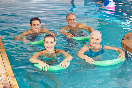 Group of happy people with swim noodles doing aqua fitness class in swimming pool