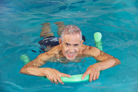 Old man swimming in water of hotel pool with swim noodle