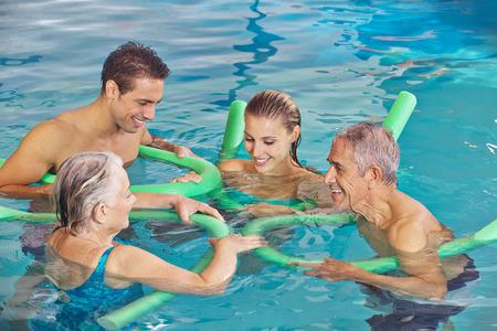 Famiglia felice con coppia senior in acqua della piscina