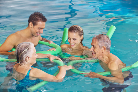 hydrotherapy: Happy family with senior couple in water of swimming pool