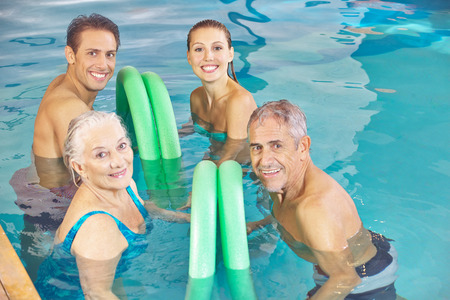 Two happy couples in aqua fitness class in a swimming pool with swim noodles