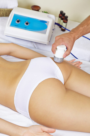 muscle formation: Woman getting electric massage at buttocks against cellulite in spa