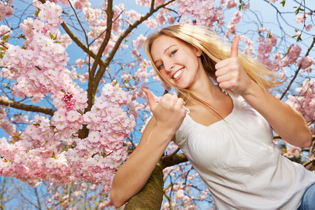 Happy woman holding both thumbs up in spring in a blooming cherry tree
