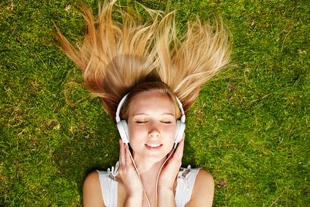 Mädchen, das Musik-Streaming mit Kopfhörern im Sommer auf einer Wiese