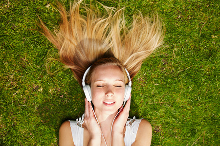 oir: Muchacha que escucha la música con los auriculares de streaming en verano en un prado Foto de archivo