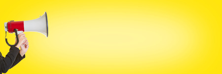 speaking tube: Business woman screaming into megaphone in front of yellow background