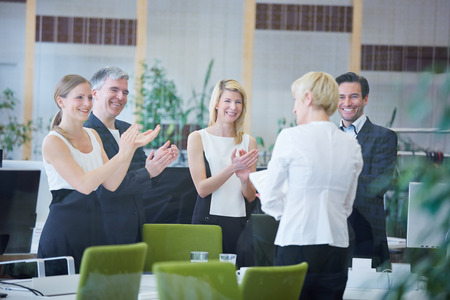 praise: Happy team of business people in office giving applause