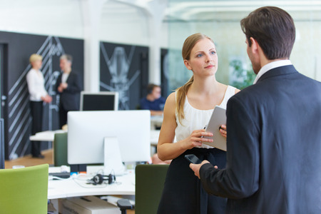 lady boss: Man and woman in office talking to each other in a break Stock Photo