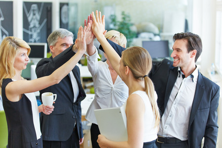 job satisfaction: Happy business team making high five with their hands in the office