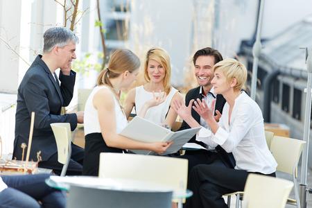 屋外のコーヒー ショップでのビジネスについて話している人々 のグループ