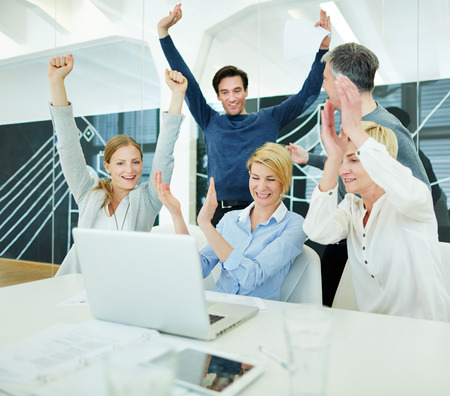 group solution: Group of happy business people cheering in office in front of computer