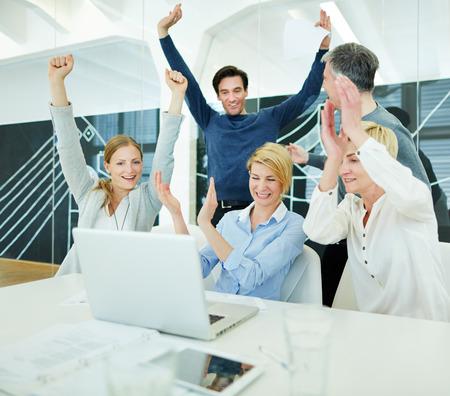 Un groupe de gens d'affaires heureux applaudir dans le bureau en face de l'ordinateur