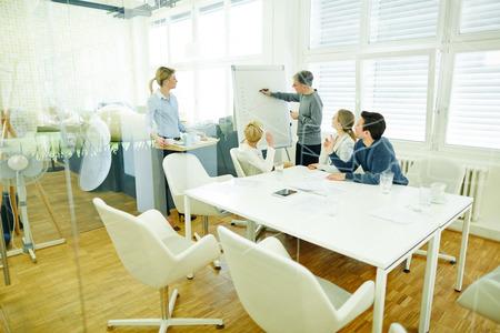 Uomo alla lavagna a fogli mobili in riunione di lavoro in una sala conferenze