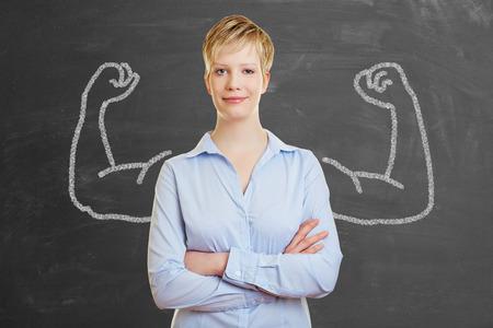 Femme d'affaires forte avec des muscles de craie devant un tableau noir Banque d'images