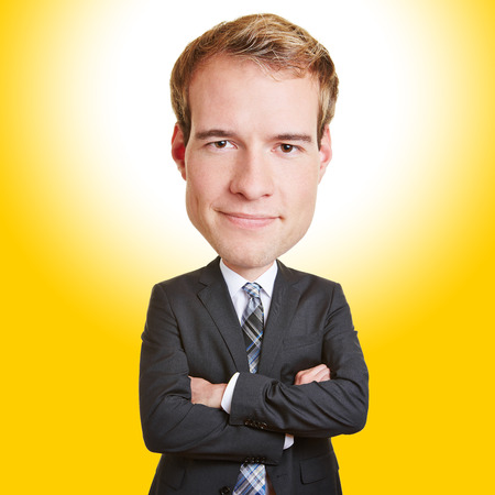 Funny smiling business man with a big head in front of a yellow background photo