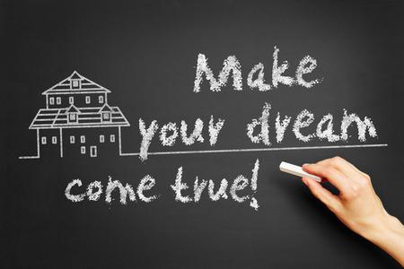 """Hand schreibt """"Machen Sie Ihren Traum wahr!"""" auf Tafel"""