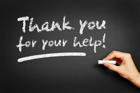 """Main écrit """"Merci pour votre aide!"""" sur le tableau noir"""