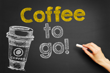 Hand writes Coffee to go! on blackboard