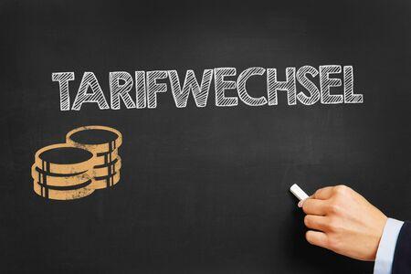 electricity tariff: Hand writes in German Tarifwechsel (tariff change) on blackboard