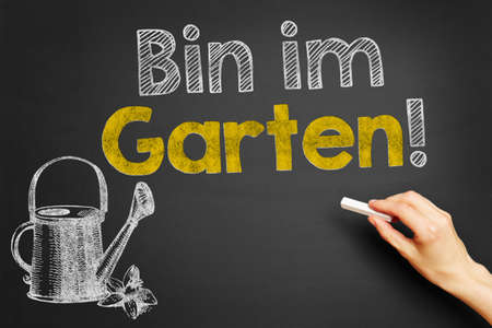 garten: Hand writes in German Bin im Garten! (Im in the garden!) on blackboard