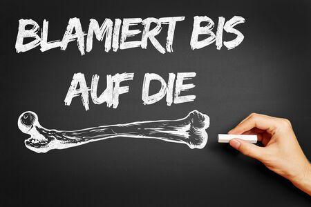 oneself: Hand writing the German saying Blamiert bis auf die Knochen (make a fool of oneself) on a blackboard Stock Photo