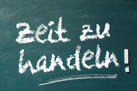 sustained: German expression Zeit zu handeln! (Time to act!) on blackboard