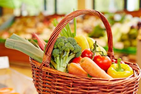 canastas con frutas: Verduras frescas coloridos en una cesta de la compra en un supermercado