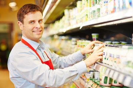 vendedor: Sonriendo vendedor organizar los productos lácteos en estante del supermercado