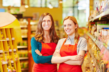 saleswomen: Two friendly saleswomen smiling in a supermarket with her arms crossed Stock Photo