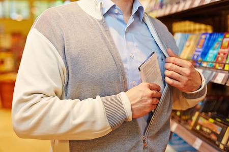 ladron: Shoplifter robar barra de chocolate en un supermercado Foto de archivo