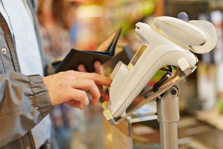 tiendas de comida: Hombre escribir su contraseña PIN en la caja del supermercado en el lector de tarjetas Foto de archivo