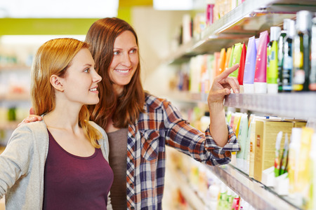 skin care products: Mother giving her daughter shopping advice in a drugstore