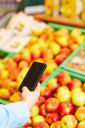 Man taking pictures of fresh apples with his smartphone in a supermarket photo