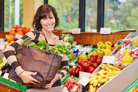 tiendas de comida: Mujer mayor sonriente con el bolso lleno de verduras frescas en un supermercado